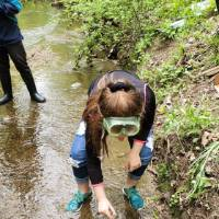 Student stands in stream and grabs sample of water